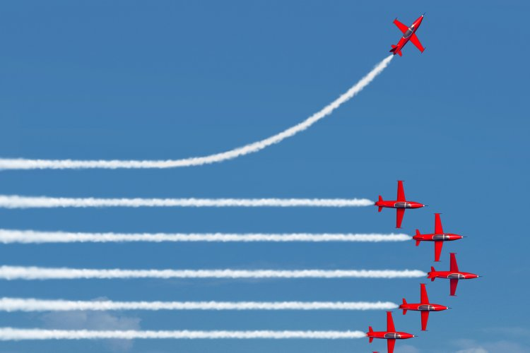 Planes flying in a row with one plane going in it a different direction
