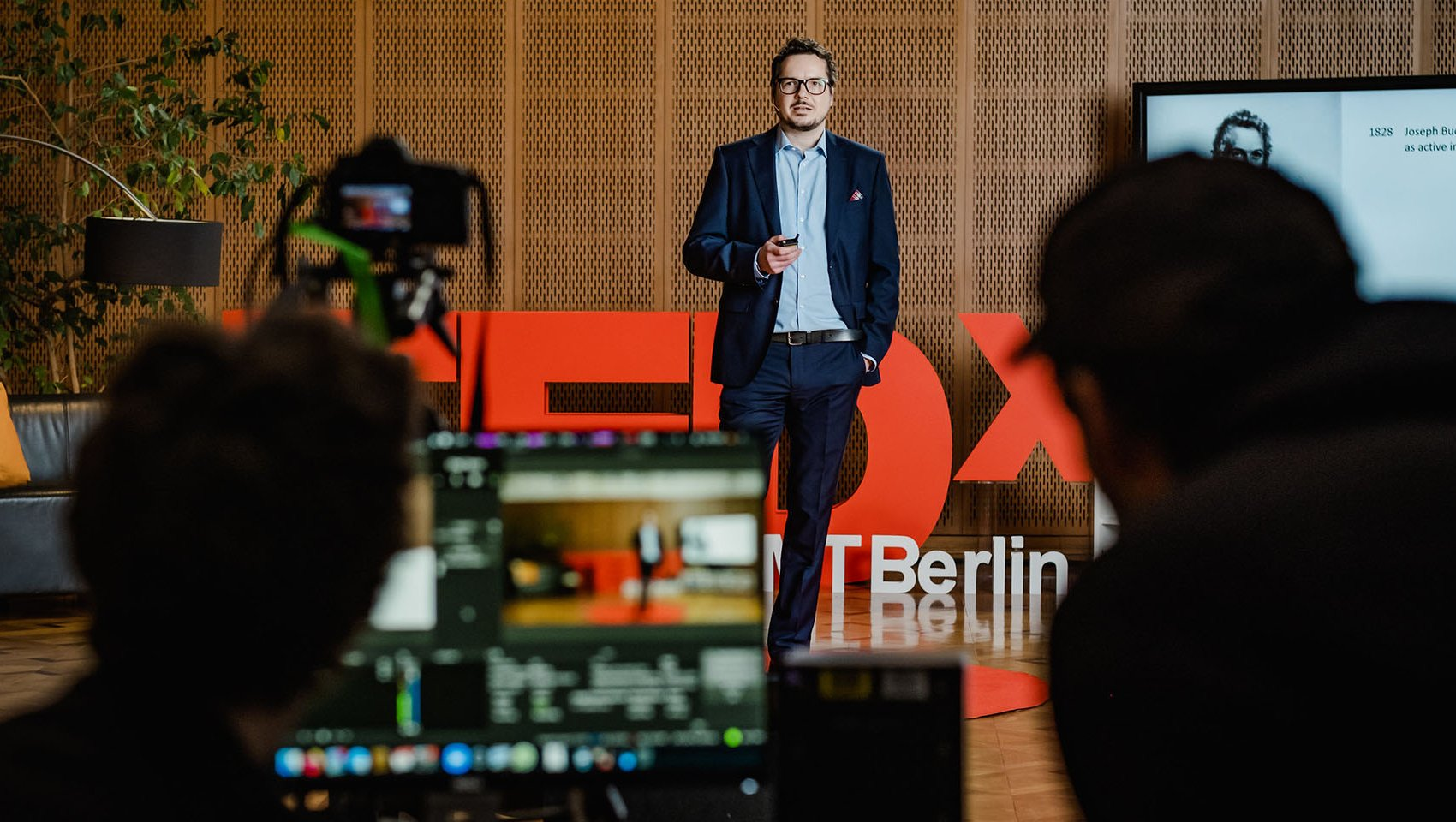 Stefan Wagner speaking at TEDx event at ESMT with blurred view of camera and camera man in front of the stage